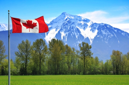 Canadian flag in front of te snow capped Rocky Mountains, British Columbia, Canada.